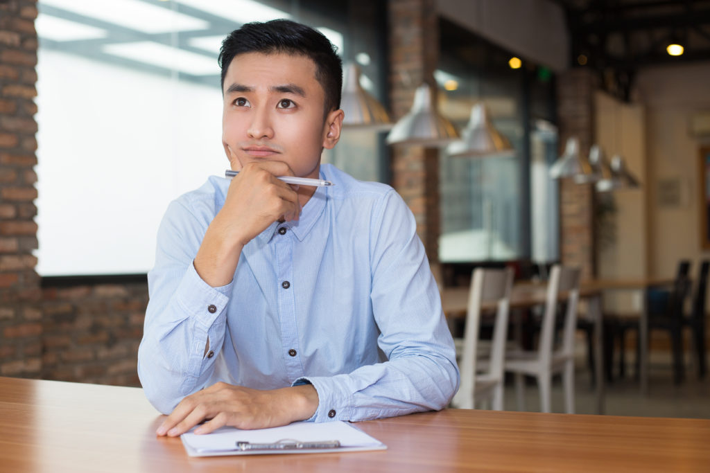 Closeup portrait of young Asian man thinking on project and sitting at table with clipboard and blurred cafe interior in background