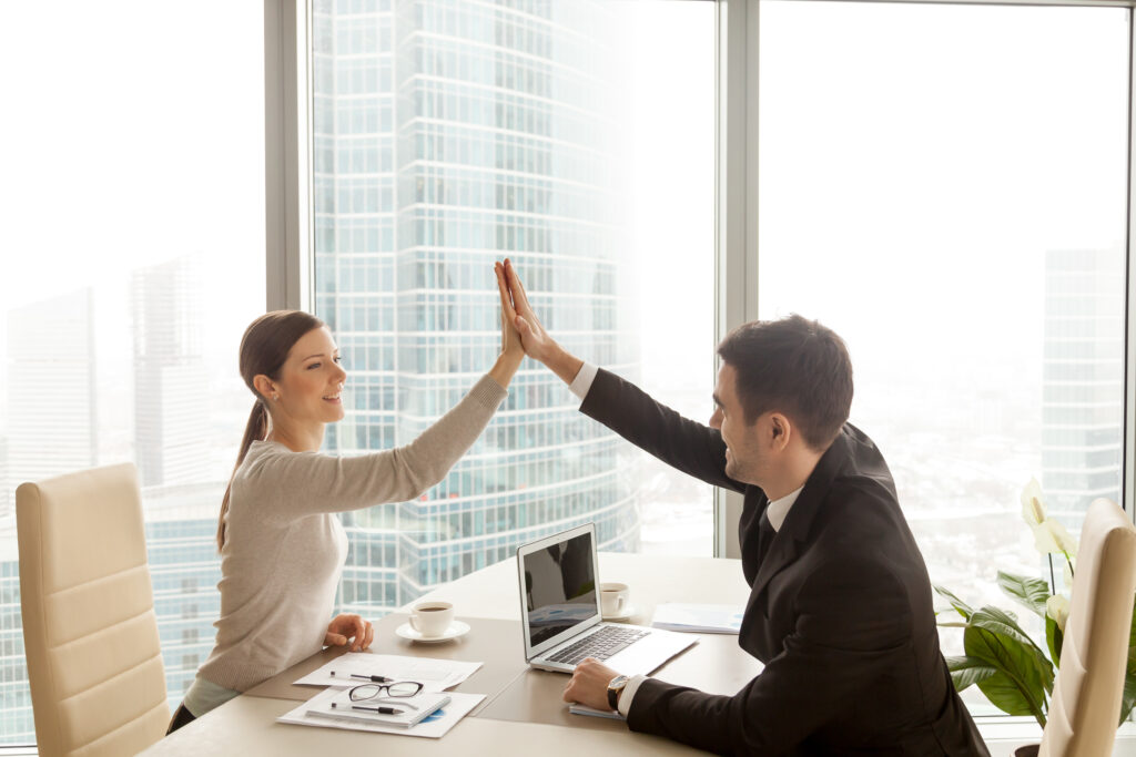 Businessman giving high five to businesswoman at office, partners celebrating good successful teamwork result, business team happy with job well-done, business achievement, company growth, side view